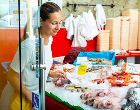Portrait of young woman choosing fresh seafood from large assortment at fish shop