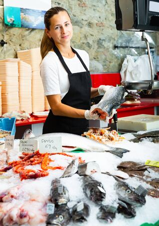 Glad female worker of fish shop in apron offering fresh raw salmon for sale Banque d'images