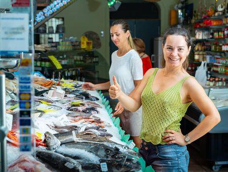 Portrait d'une cliente satisfaite et joyeuse, debout près de la vitrine de fruits de mer de la poissonnerie