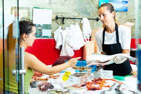 Vendeuse ordinaire de poissonnerie offrant des fruits de mer à une cliente