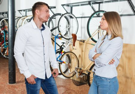 Man with woman are choosing modern bicycle and disputing in the bike store.