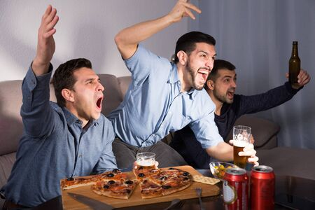 Three happy men emotionally watching sports on tv while drinking beer with pizza at home Reklamní fotografie