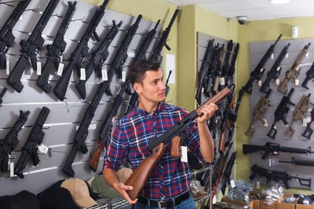 Positive young man choosing air weapon in military shop