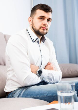 Young sad unhappy man feeling distressed and lonely alone at home