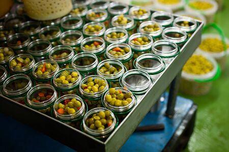 Open glass jars with olives - preparation for canning