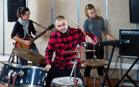 Music garage band with expressive male drummer rehearsing on rehearsal base Stock Photo
