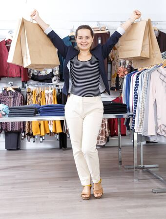 Portrait of modern stylish woman with lot of paper shopping bags in her hands in clothing boutique Stock Photo