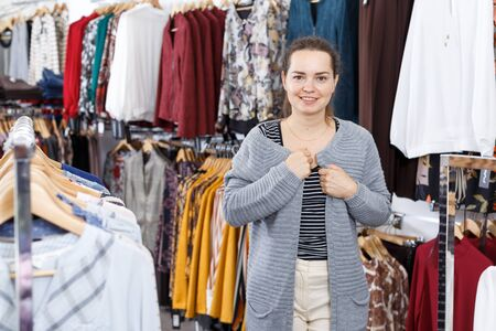 Smiling young woman trying various clothes in hall of showroom Stock Photo