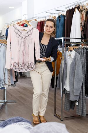 Cheerful attractive woman choosing new clothes in showroom