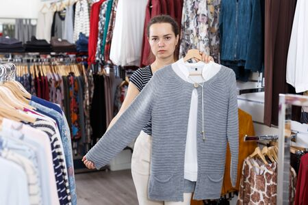 Young attractive woman choosing new clothes in clothing shop