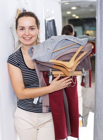 Smiling young woman trying various clothes in dressing room of clothing store