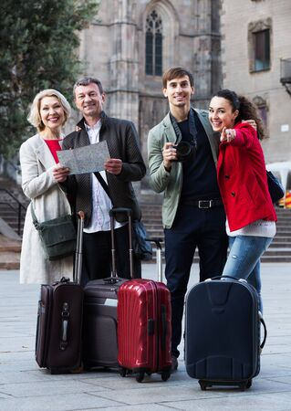 Family of four tourists with baggage reading city map and sightseeing outdoors