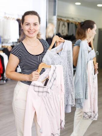 Attractive woman demonstrating blouse on hanger in clothing store