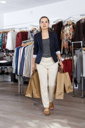 Attractive young woman holding paper shopping bags in clothing shop