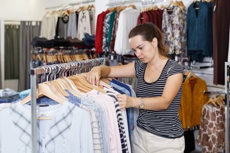 Young cheerful woman shopping in clothing boutique