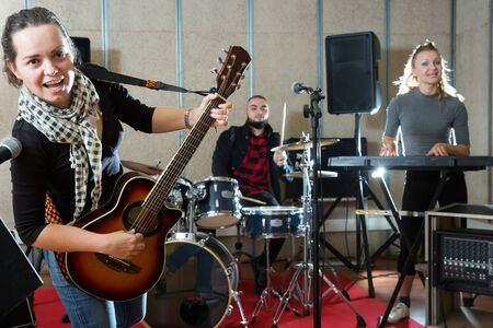 Rehearsal of music band. Young girl guitar player and singer practicing with band members in recording studio