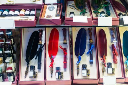 Vintage colorful quill pens, ink and other writing implements on showcase of souvenir shop
