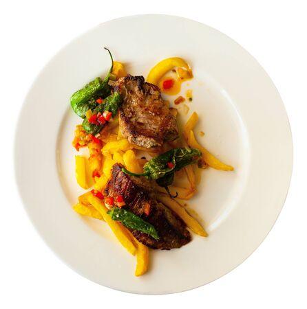 Gegrilltes Rindfleisch mit Pfeffersauce, serviert mit Pommes Frites und grünem Paprika. Auf weißem Hintergrund isoliert Standard-Bild