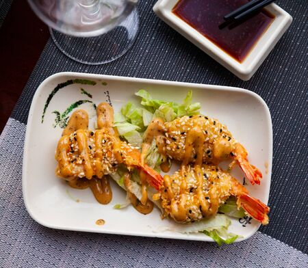 Roasted shrimps in batter of tempura flour and sesame on lettuce cushion and sauce, japanese cuisine