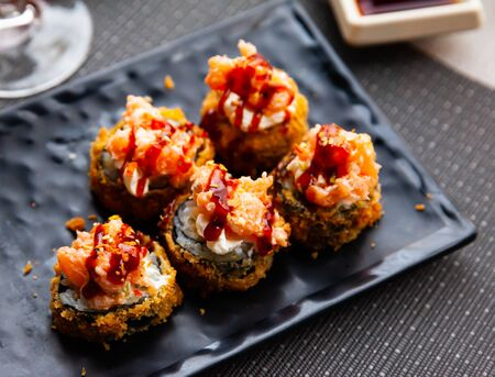 Hot fried futomaki topped with chopped salmon and delicate cream cheese. Traditional Japanese sushi Banco de Imagens