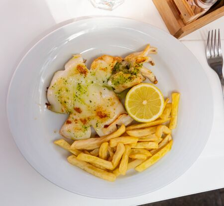 Appetizing fried sepia flavoured with savory green sauce served on white plate with fries and lemon