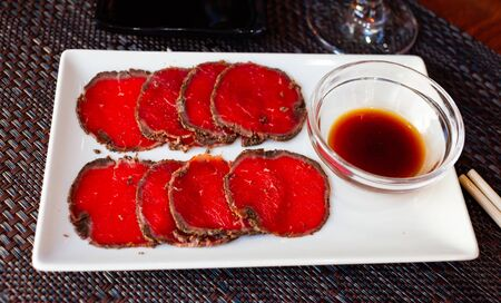 Thinly sliced raw beef, Korean dish Yuksashimi served with soy sauce