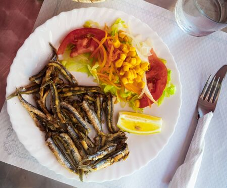 Healthy seafood. Baked anchovies served with vegetable garnish of lettuce, tomatoes, sweet corn and lemon