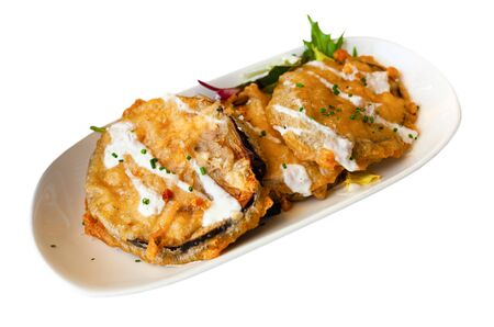 Battered eggplant slices served with yogurt sauce on white plate. Isolated over white background