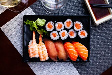 Appetizing sushi set from salmon makizushi and nigirizushi with various toppings served on black plate with wasabi and soy sauce. Popular Japanese dish Banco de Imagens