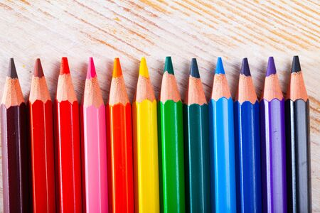 Multicolored pencils on wooden background. Concept of artistic education and art