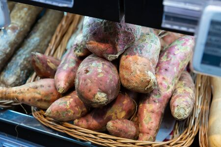 Raw sweet potato tubers for sale on market counter. Vegetarian food concept