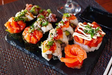 Assorted sushi set from gunkans, uramakizushi and salmon sashimi served with wasabi and soy sauce. Popular Japanese dish