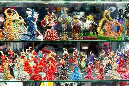 Variety of handcrafted ceramic figurines of Spanish flamenco dancers on shelves of souvenir shop