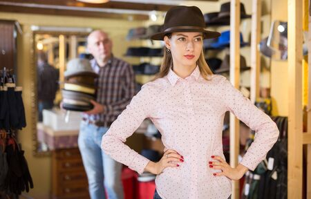 Portrait of elegant woman trying on new hat in shop, salesman ready to help on background Stock fotó
