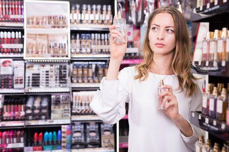 Female customer testing perfume in makeup store