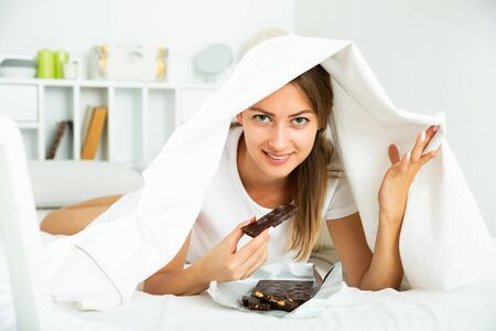 Happy girl hiding under sheet with sweets indoors