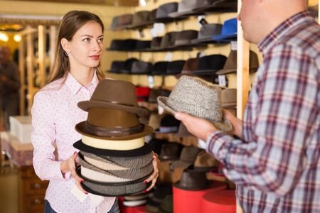 Portrait of young confident salesgirl helping male customer to choose new hat in shop