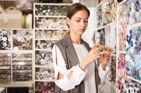 Skillful young seamstress looking for buttons for sewing clothes in haberdasher shop