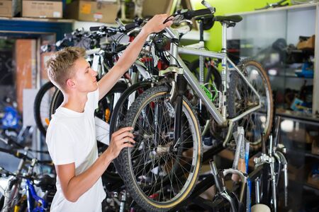 Young buyer male checking tire on wheel in the shop