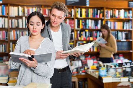 Positive smiling girl reading book in bookstore while guy looking at her book over her shoulder