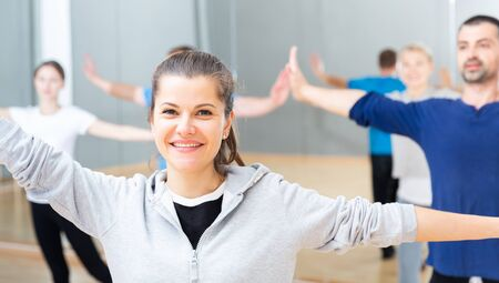 Positive young woman trainer doing aerobics exercises with group of adult people in dance center