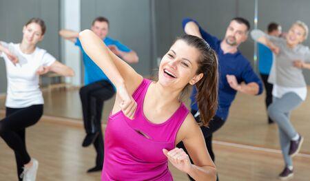 Portrait of dancing girl practicing vigorous swing during group training in dance studio Stockfoto