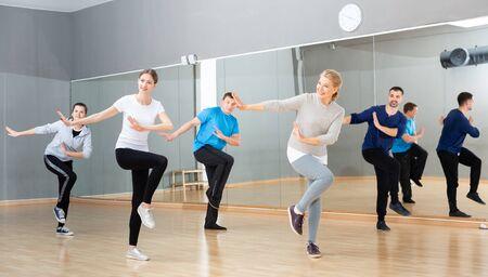 Cours de danse pour adultes, hommes et femmes jeunes et matures positifs s'entraînant dans un studio de danse Banque d'images