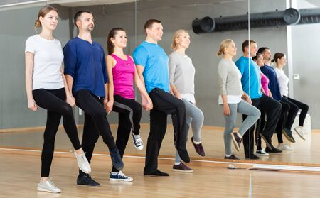 Group of adult people lining up while fulfilling dance movements of folk Celtic dance in choreography class