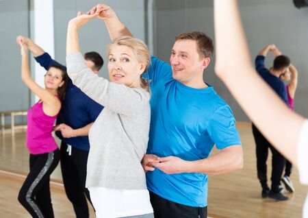 Positive mature woman learning to dance kizomba with partner in dancing class