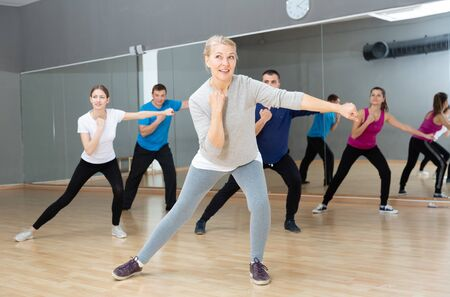 Positive mature blonde doing aerobics exercises in group of adult people, training in fitness center
