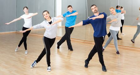 Portrait of dancing people practicing vigorous swing during group training in dance studio