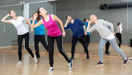 Dance class for adult people, positive young and mature men and women training in dance studio Standard-Bild