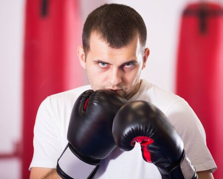 Portrait of young athlete male training in colored boxing gloves