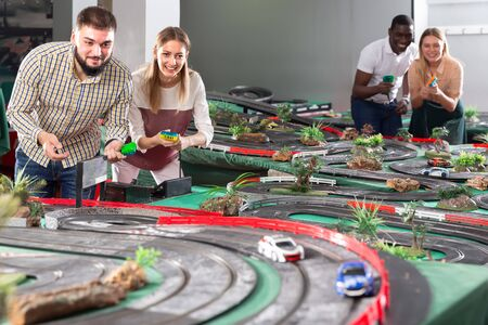 Young couples play a game slot car racing track